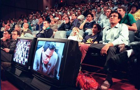 Chess fans watch in an auditorium progress of the
